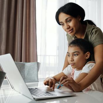 Mother helps daughter use laptop.